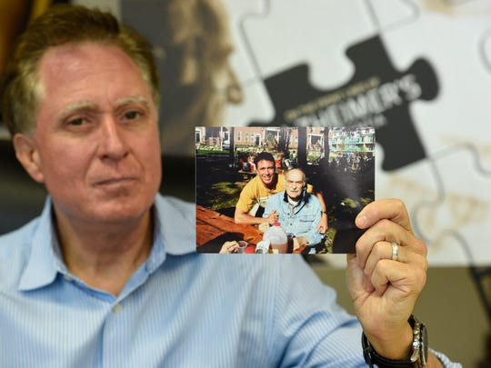 Keith Famie holds a photo of he and his dad.