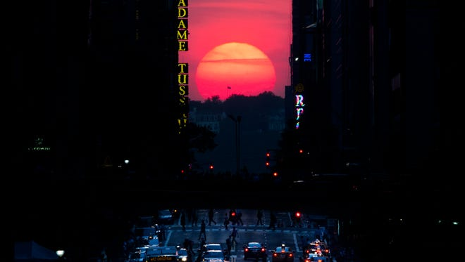"""The sun sets along 42nd Street in Manhattan during an annual phenomenon known as """"Manhattanhenge,"""" when the sun aligns perfectly with the city's transit grid on May 29, 2013, in New York."""