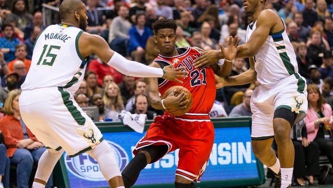 Chicago Bulls guard Jimmy Butler (21) drives for the basket between Milwaukee Bucks center Greg Monroe (15) and forward Damien Inglis (17).