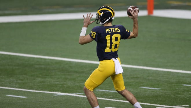 Michigan Wolverines QB Brandon Peters throws passes during a practice held at Ford Field in Detroit on Saturday, March 26, 2016.