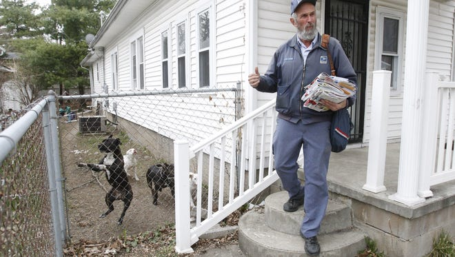 Connersville mail carrier Stan Howard gets the attention of four dogs on his route.