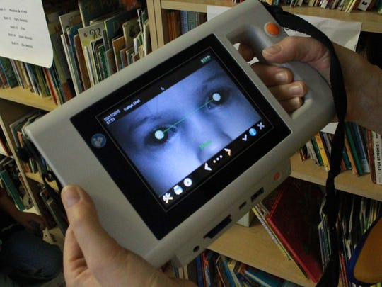 A Lions Club member demonstrates the Plusoptix S12C Mobile Vision Screener. The club has screened more than 400 children this year to detect eye problems early.