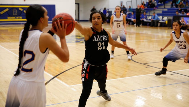 Aztec's Myra McCaskill looks to contest a 3-point shot by Bloomfield's Brandi Alcantar during a District 1-5A game on Jan. 20 at Bobcat Gym. McCaskill and Alcantar will play in the 5A/6A All-Star game on June 8.
