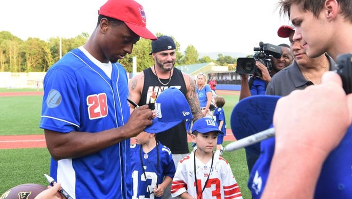 New York Giant Eli Apple signs autographs before the celebrity softball game held at Dutchess Stadium.