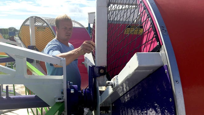 Adam Brotzman of Snyder's Amusements demonstrates how R-keys and other fasteners and assembly pieces are checked to ensure the safety of the Rok N Rol ride at the Elizabethtown Fair on Sunday, Aug. 21.
