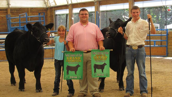 Karli Berkheimer (Mechanicsburg), left, exhibited the Grand Champion Market Steer. Daniel Rohrbaugh (Seven Valleys), far right, exhibited the Reserve Market Steer. They are pictured with Judge, Troy Longenecker (Lebanon County).