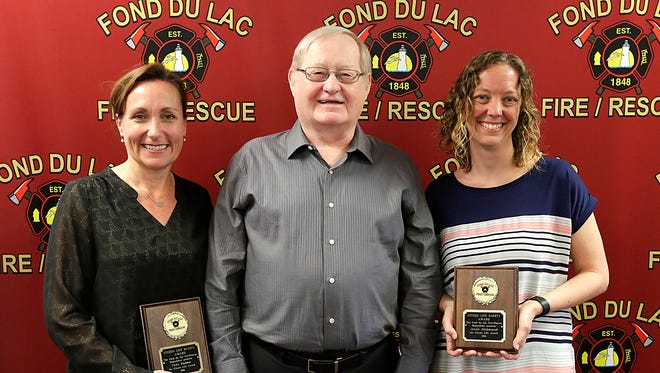 Vicky Raddatz (left) and Jennie Mildebrandt (right) hold their Citizen Life Safety awards they received from the Fond du Lac Fire/Rescue for their part in saving the life of Gary Gerner (center) in January of last year after he collapsed while on an elliptical machine at the Fond du Lac Family YMCA.