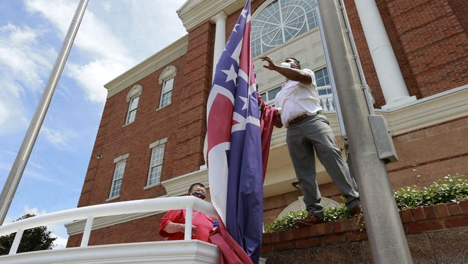 City of Tupelo Community Outreach Coordinator Marcus Gary takes down the Mississippi state flag that flew over the City Hall of Tupelo one last time Monday.