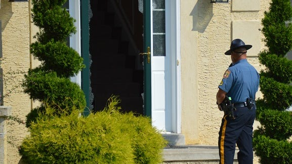 A state trooper stands near a broken door on Powell Court on Wednesday afternoon after a trooper was shot at the residence earlier in the day.