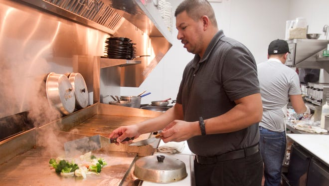 Red Olive head chef Juan Mireles prepares a shrimp stir fry in the kitchen of the newly opened Genoa Township restaurant.