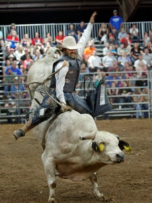 Trent Cormier hangs on for an eight-second ride during the 27th annual Kiwanis Rodeo at the Montgomery County 4H Arena in 2014.