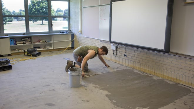 Corey Muxlow spreads a leveling compound on the floor of a classroom before laying new carpeting Tuesday, July 21, 2015 at Yale Elementary School. Voters will be asked to renew the 1 miLl sinking fund on Aug. 4, which will generate approximately $1.8 million over five years.
