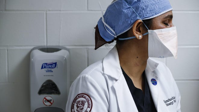 A health care worker pauses as she walks through the emergency department at NYC Health + Hospitals Metropolitan, May 27 in New York.