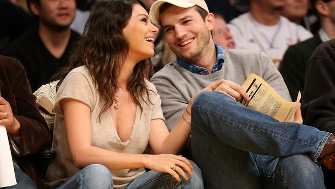 Mila Kunis and Ashton Kutcher take in a game between the Oklahoma City Thunder and the Los Angeles Lakers at Staples Center on December 19, 2014 in Los Angeles.