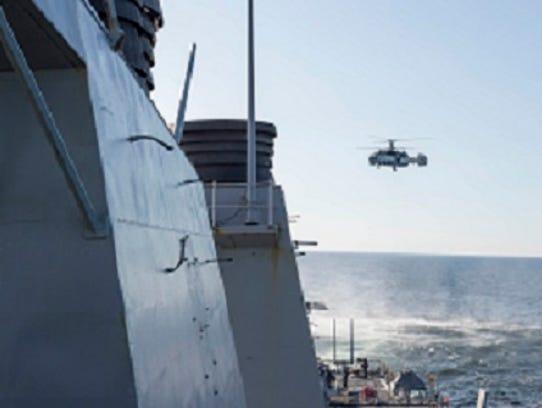 A Russian Kamov KA-27 Helix closely surveils the Arleigh