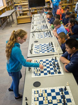 One of New Mexico's highest rated chess champions, 11-year-old Camino Real Middle School 6th-grader Sophia Moore, left, plays 8 games of chess simultaneously against students from Loma Heights Elementary School in Loma's library, April 29, 2016.