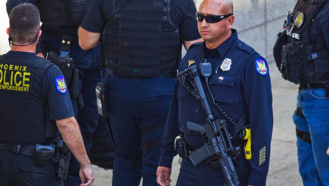 Phoenix police officers gather at the scene of the shooting in downtown Phoenix.