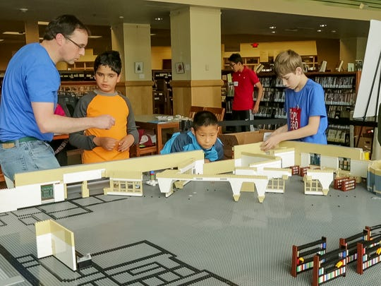 From left, Peter McCracken, Michael Perelstein, 8, Terry Wang, 9, and McCracken's son Andrew, 12, all of Ithaca, work to assemble the Lego mini figure scale model of the Tompkins County Public Library.