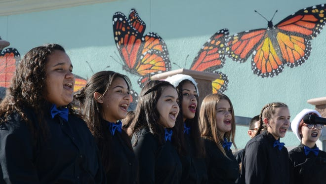 Desert Ridge Academy choir students sing for the dedication ceremony of a butterfly mural painted by artist Walter Lab.