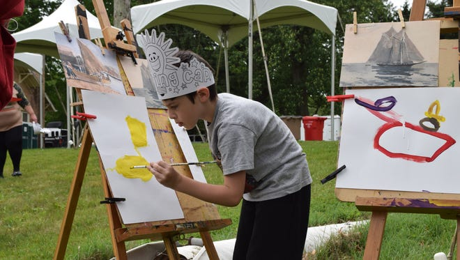 Jorden Marolda, 7, of Vineland paints a picture at the Magnolia Studios Art tent at Vineland Founder's Day.