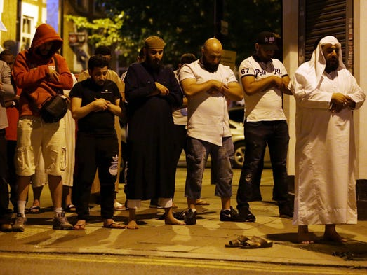 Muslims pray on a sidewalk in the Finsbury Park area
