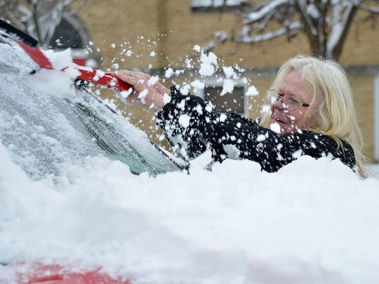 Lori Hawbaker clears snow off a red Ford F-350 pickup, Jan. 13, 2019, on Howard Street in Hagerstown, Md. Hawbaker said she was OK with the snow, as long as it's the last of the season.