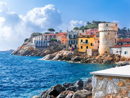 """The perfect tiny seaside village of """"Giglio Porto"""" with multi colored houses, an ancient defensive tower and a rocky coastline against a deep blue Mediterranean sea. - Giglio Island, Tuscany, Italy"""