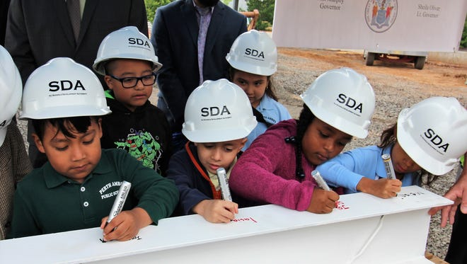 Perth Amboy school children sign beam for the new Seaman Avenue Elementary School.