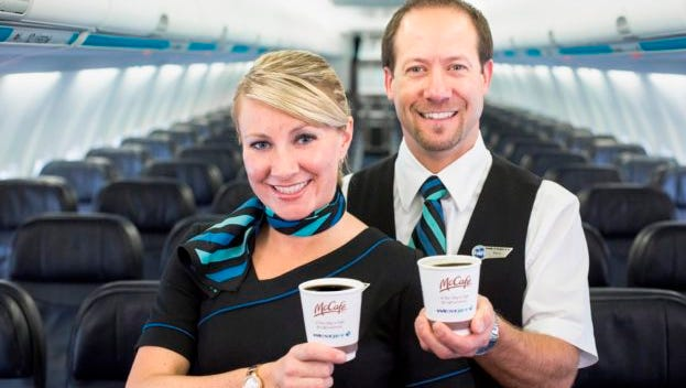 In a promotional photo provided by the airline, WestJet attendants show off the new McCafe-branded coffee cups that will be used on the carrier's flights.