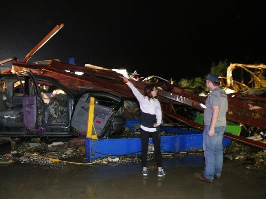 Ernestine Cook of Canton, Texas, points out the damage to spotter Michael Search of Henderson, Texas, as they inspect the damage done to the I-20 Dodge dealership after a tornado hit Canton, Texas, Saturday, April 29, 2017. Cars and trucks were piled high and the service area was destroyed.