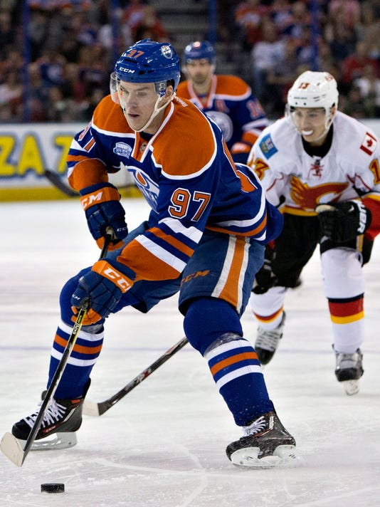 Calgary Flames' Johnny Gaudreau (13) chases Edmonton Oilers' Connor McDavid (97) during the second period of an NHL game in Edmonton, Alberta, on Saturday, April 2, 2016. (Jason Franson/The Canadian Press via AP)