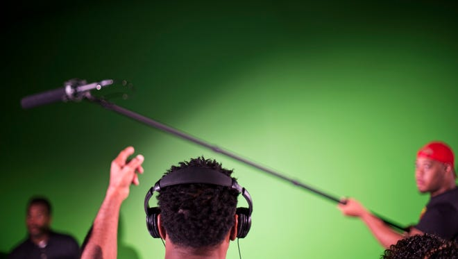 Student Dexter Carr, of Forest Park, Georgia instructs a boom microphone to be raised higher while listening to its recording through headphones during a digital film technician program introductory class at Clayton State University in Jonesboro, Georgia in 2015.