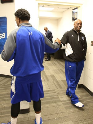 Hampton coach Edward Joyner Jr. shakes hands with guard Reginald Johnson (34) in the locker room before playing Kentucky on Thursday in the NCAA tournament second round.