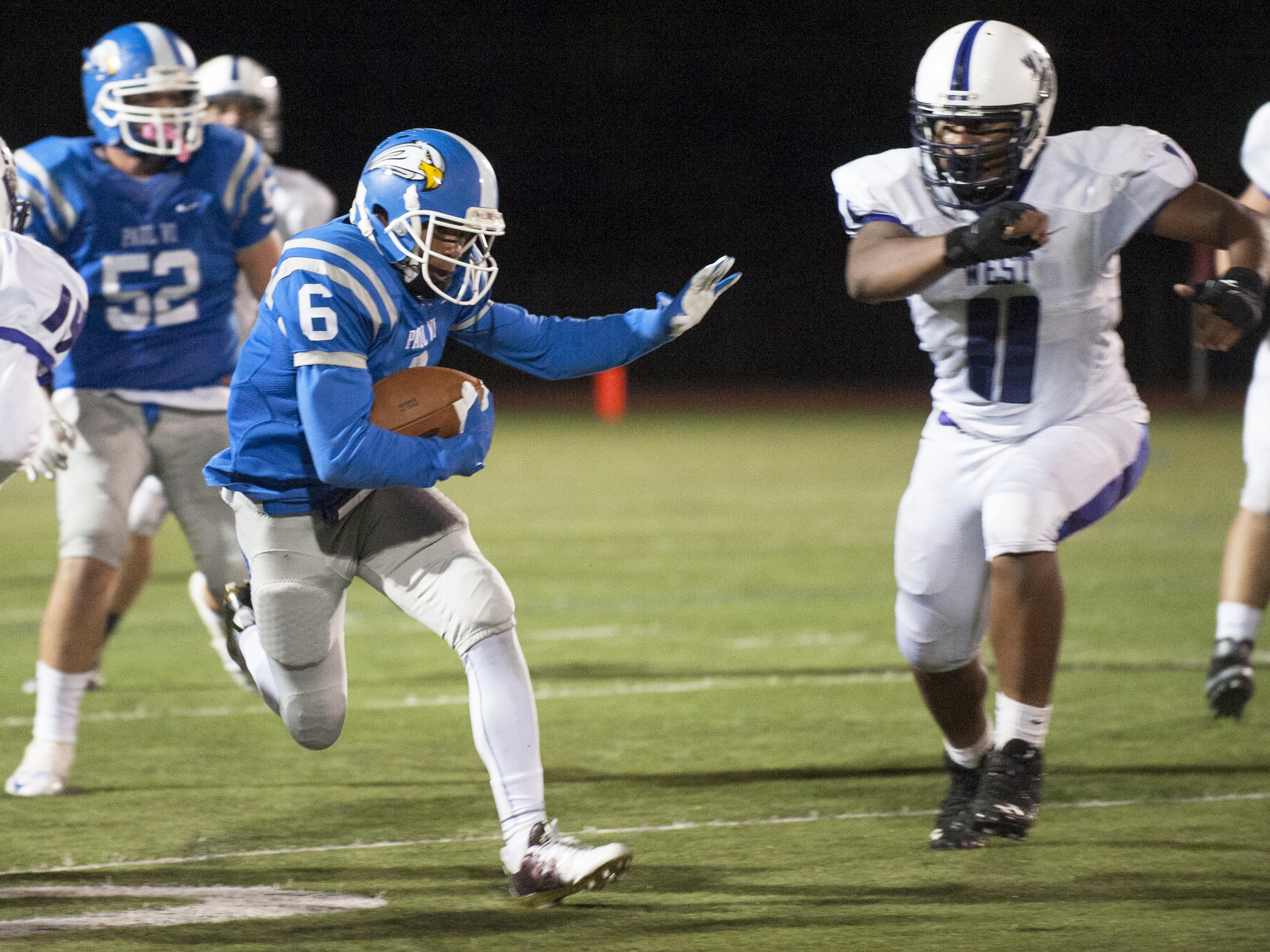 Paul VI's Stefone Moore-Green, left, tries to outrun Cherry Hill West's Lorenzo Hernandez, right, during the second quarter of Friday's game. The host Eagles prevailed with a 23-6.