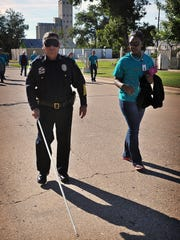 Wichita Falls Police Chief Maneul Borrego, assisted by D'Andrea Lee, an orientation and mobility specialist, participates in White Cane Day, hosted by Beacon Lighthouse. The event gives members of the community a blindfold and a cane to walk a mile as a visually impaired person.