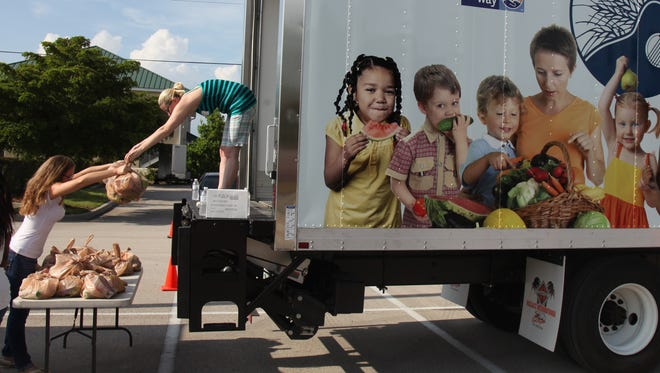Volunteers Ashley Lavelle, right, and Sarah Prater, remove perishable food from a refrigerated truck while handing it out to families at Faith Presbyterian Church in Cape Coral on Wednesday.