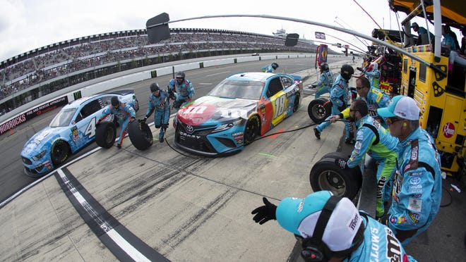 Kyle Busch (18) and Kevin Harvick (4) make pit stops during a NASCAR Cup Series race at Pocono Raceway, Sunday, June 2, 2019, in Long Pond.