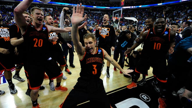 Mercer Bears guard Kevin Canevari (3), forward Jakob Gollon (20) and guard Ike Nwamu (10) celebrates after beating the Duke Blue Devils in a men's college basketball game during the second round of the 2014 NCAA Tournament at PNC Arena.