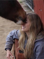 Lexi and Chief: Local singer Lexi Tucker receives a thank-you nuzzle for her music from her horse Chief.