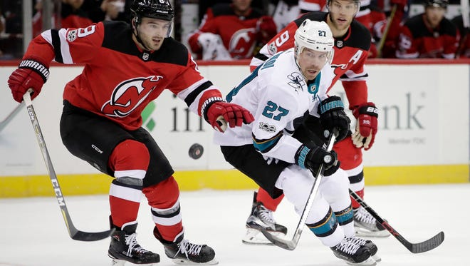 New Jersey Devils defenseman Will Butcher (8) and San Jose Sharks right wing Joonas Donskoi (27), of Finland, compete for the puck during the first period of an NHL hockey game, Friday, Oct. 20, 2017, in Newark, N.J.