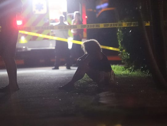 A woman grieves at an officer involved shooting on