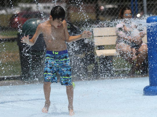 Bryson Pena, 7, of Garfield beats the heat at Spray Park on Jewell St.  Temperatures Monday reached the upper 90's while the real feel climbed to the triple digits. Temperatures Tuesday are forecast to break 90 degrees again but possible thunderstorms could put an end to the heat wave. Monday, July 2, 2018