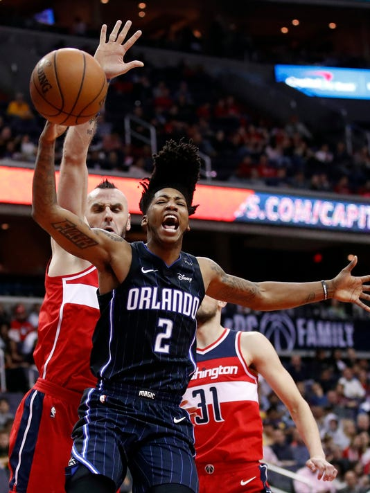 Orlando Magic guard Elfrid Payton (2) reacts after he was fouled while shooting against Washington Wizards center Marcin Gortat (13), from Poland, and forward Tomas Satoransky (31), from the Czech Republic, during the first half of an NBA basketball game Friday, Jan. 12, 2018, in Washington. (AP Photo/Alex Brandon)