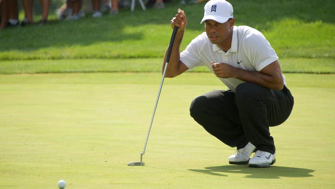 Tiger Woods check his ball before putting in the first round of the Quicken Loans National golf tournament at Robert Trent Jones Golf Club.