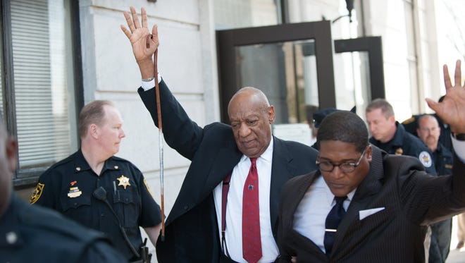 Bill Cosby gestures as he leaves the Montgomery County Courthouse.
