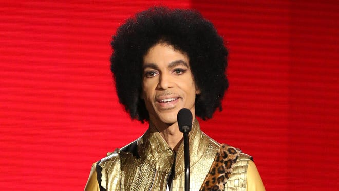 In this Nov. 22, 2015 file photo, Prince presents the award for favorite album in soul/R&B at the American Music Awards in Los Angeles.