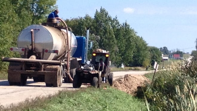 Contractors transfer spilled manure into waiting trucks on Wednesday along Door County D in the town of Brussels.