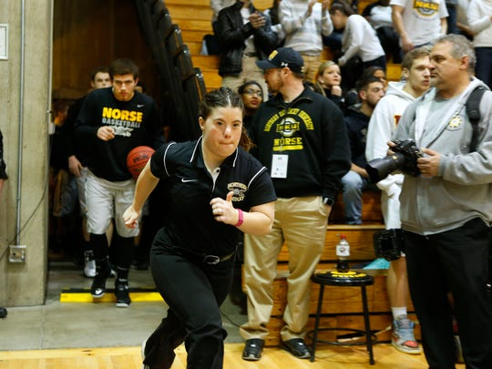 Jillian Daugherty, 25, men's basketball manager for Northern Kentucky University, runs onto the court during the team's Atlantic Sun Basketball Championship against Lipscomb University. The Norse were defeated in overtime, 76-73.