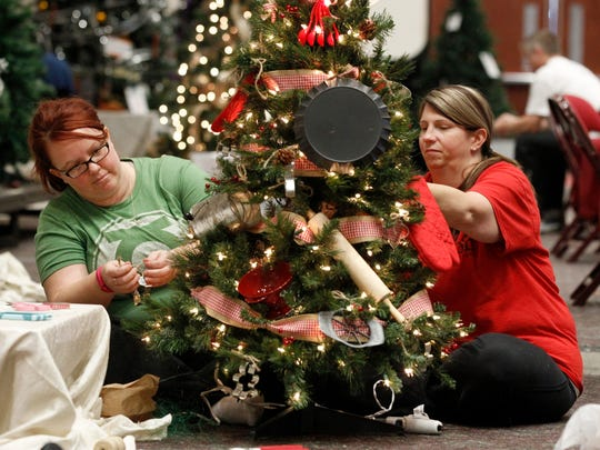 Kelly Bowen (left) and Leann Stephens decorate a Christmas