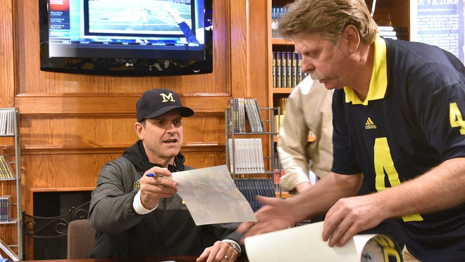 Michigan football coach Jim Harbaugh signs autographs for fans at the M Den store in downtown Ann Arbor.